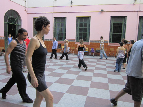 people practicing their tango walk, in their eje (axis) at a psicotango workshop in buenos aires. psicotango is a free workshop where people explore deeper dimensions of tango